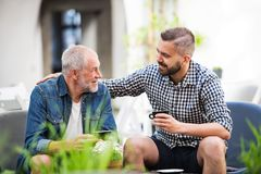 Un fils adulte de hippie et un père supérieur avec une tasse de café dans un café extérieur Photos stock
