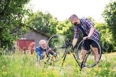 Un fils adulte de hippie et un père supérieur réparant la bicyclette dehors un jour ensoleillé Photographie stock