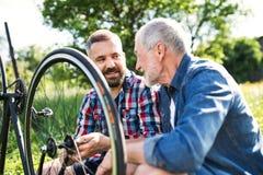 Un fils adulte de hippie et un père supérieur réparant la bicyclette dehors un jour ensoleillé Images stock
