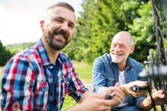 Un fils adulte de hippie et un père supérieur réparant la bicyclette dehors un jour ensoleillé Images libres de droits