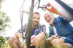 Un fils adulte de hippie et un père supérieur réparant la bicyclette dehors un jour ensoleillé Photo stock