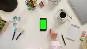 Un finger que toca Smartphone con una pantalla verde almacen de metraje de vídeo