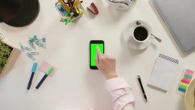 Un finger que toca Smartphone con una pantalla verde metrajes