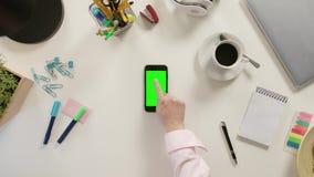 Un finger que toca Smartphone con una pantalla verde almacen de video