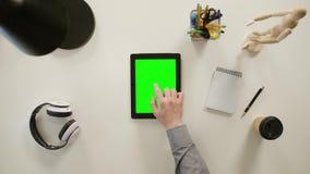 Un finger que toca una pantalla verde del iPad almacen de metraje de vídeo