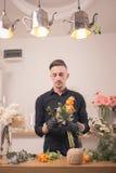 Un fiorista dell'uomo, facente mazzo, negozio di fiore all'interno Immagini Stock Libere da Diritti