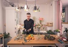 Un fiorista dell'uomo, sistemante i fiori, negozio di fiore all'interno Fotografie Stock
