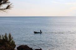 Un Fisher nella barca vicino alla riva di mare adriatica (Montenegro, inverno) Fotografia Stock