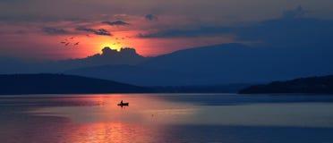 Un fishman está yendo a casa en la puesta del sol fotografía de archivo libre de regalías