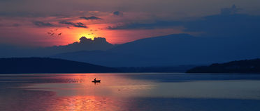 Un fishman s'attaque à la maison au coucher du soleil photographie stock libre de droits