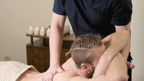 Un fisioterapeuta de sexo masculino hace un poder que estira para un paciente masculino a un inconformista barbudo joven en un cu metrajes