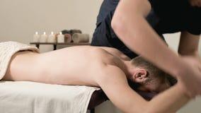 Un fisioterapeuta de sexo masculino hace un poder que estira para un paciente masculino a un inconformista barbudo joven en un cu almacen de video