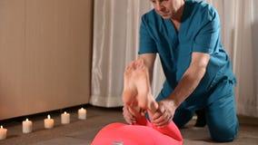 Un fisioterapista maschio sta allungando i giunti di ginocchio ad un paziente della ragazza Terapia manuale di benessere stock footage