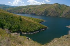 Un fiume circondato dalle alte montagne Fotografie Stock