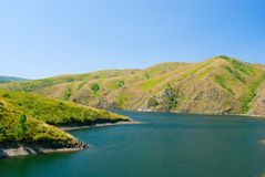 Un fiume circondato dalle alte montagne Fotografia Stock