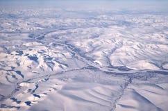 Un fiume congelato che passa ghiaccio e neve nell'Alaska Immagine Stock
