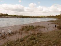 Un fiume del canale navigabile attraverso il Regno Unito con bassa marea e gli uccelli che guadano i Immagini Stock Libere da Diritti