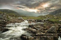 Un fiume scorrente con un contesto della montagna Fotografia Stock Libera da Diritti