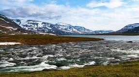 Un fiume selvaggio artico che entra da un lago nelle montagne nevose Immagine Stock