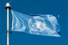UN Flag. United Nation flag against a clear blue sky Stock Images
