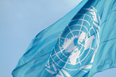 UN flag waving. The flag of the United Nation waving in the wind against a spring blue sky Royalty Free Stock Image