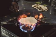 Un flatbread indio del roti que cocina en un fuego del carbón imagen de archivo