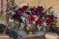 Un florero determinado de la tabla con las flores adorna en púrpura y rojo Fotos de archivo