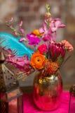 Un florero determinado de la tabla con las flores adorna en púrpura y rosa Imagenes de archivo
