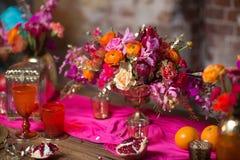 Un florero determinado de la tabla con las flores adorna en púrpura y rosa Imagen de archivo libre de regalías