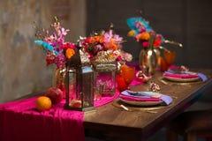 Un florero determinado de la tabla con las flores, placas adorna en púrpura y rosa Fotos de archivo libres de regalías