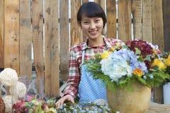 Un florista asiático bastante joven Working en el jardín Fotos de archivo
