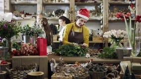 Un florista en un sombrero de la Navidad hace un ramo de ramas del abeto, cámara va de tj izquierdo la derecha almacen de metraje de vídeo