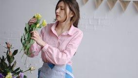 Un florista joven escoge el eustoma de las flores y los examina para su arreglo fotos de archivo
