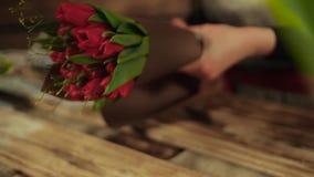Un florista joven recolecta las flores en un ramo almacen de metraje de vídeo
