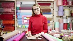 Un florista se coloca en su tienda que habla en el teléfono, escribiendo notas y examinando las fuentes de tienda ella está cansa almacen de metraje de vídeo
