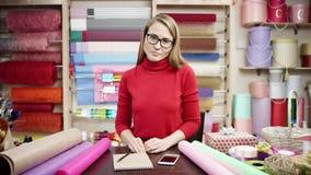 Un florista se coloca en su tienda que habla en el teléfono, escribiendo notas y examinando las fuentes de tienda almacen de video