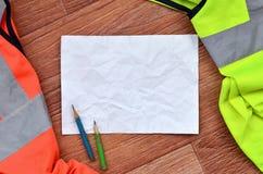 Un foglio di carta sgualcito con due matite circondate dalle uniformi funzionanti verdi ed arancio Natura morta connessa con la r immagine stock