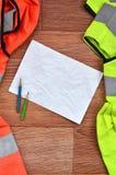 Un foglio di carta sgualcito con due matite circondate dalle uniformi funzionanti verdi ed arancio Natura morta connessa con la r immagini stock libere da diritti