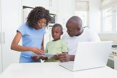 Un fonctionnement de famille et à l'aide de son ordinateur photographie stock libre de droits