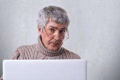 Un fonctionnement de port en verre d'homme d'affaires mûr sûr avec un ordinateur portable tout en à la maison regardant dans l'ap Image libre de droits