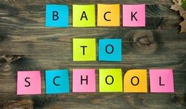 Un fond en bois avec des feuilles d'automne avec les mots de nouveau à l'école sur les autocollants colorés Image libre de droits