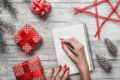 Un fond moderne d'un fond blanc de carnet de fond, et une jeune dame qui écrit un message de Noël avec un message blanc Image libre de droits