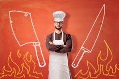 Un fondo arancio luminoso con le fiamme tirate, una mannaia, un coltello e una condizione maschio seria del cuoco nel centro immagini stock