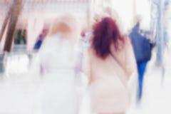 Un fondo astratto di due ragazze di nuovo noi che affrettiamo giù la via della città Mosso intenzionale Concetto delle stagioni Immagini Stock
