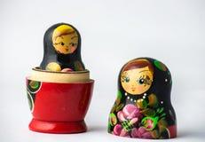 Un fondo bianco uno di due bambole di Matryoshka altro aperto dentro fotografia stock libera da diritti