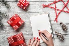 Un fondo blanco moderno de una tarjeta blanca del fondo, y una señora joven que escribe un mensaje por el Año Nuevo Imágenes de archivo libres de regalías