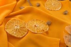 Un fondo brillante y una tela anaranjada en un estilo acogedor Rebanadas de naranja y de almendras secadas Endecha plana imagenes de archivo
