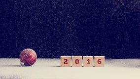 Un fondo da 2016 nuovi anni con neve che cade sull'Natale rosso Immagini Stock