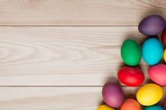 Un fondo de madera para una inscripción y un manojo de huevos de Pascua Imagen de archivo libre de regalías