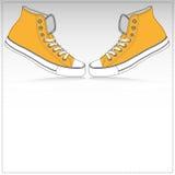 Un fondo di carta di due scarpe da tennis arancio Fotografia Stock